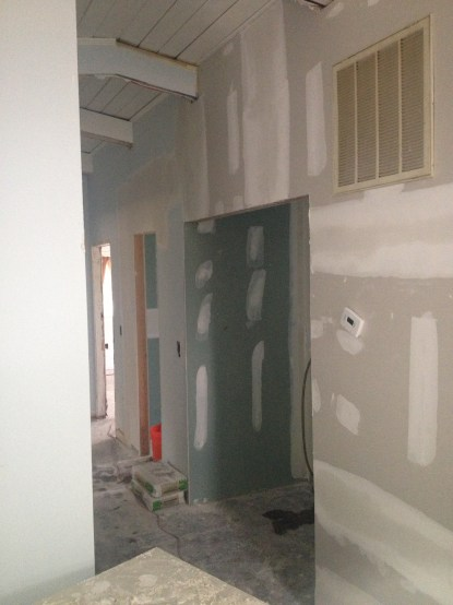to the right is a large opening where the new laundry closet is. To the left of it is the renovated bathroom doorway
