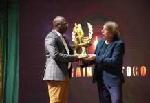 Le Col Akpovy, président de la FTF, recevant le prix spécial du Chef de l'Etat des mains de Claude le Roy, initiateur du projet