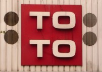 TOTO sign behind red backdrop
