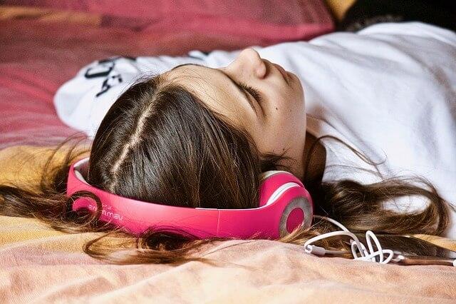 Nainen kuuntelee äänikirjaa selällään