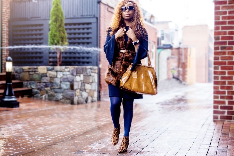 Fashion blogger in navy dress and faux fur