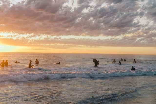 people enjoying sunset while swimming in water