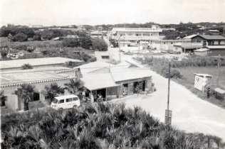 南島開発前のT字路付近(現在の郵便局近く)。奥の2階建ての建物が農協ビル