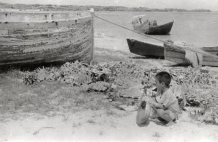 小さなザルを持って漁から帰ってくる父を待つ少年