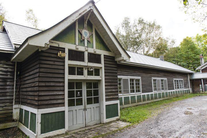 敷地の奥には年季の入った建物が。ここはもともと1928年に建てられた東川第5小学校の校舎でしたが、1983年に閉校。その2年後の1985年から、同社がリノベーションして事務所や工房、木材の倉庫として使用しています。建物の入り口の上に、今なお残る校章が当時を物語ります