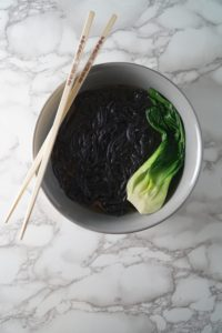 A grey bowl with chopsticks, broth, black noodles, and bok choy for a Asian Chicken noodle soup bowl
