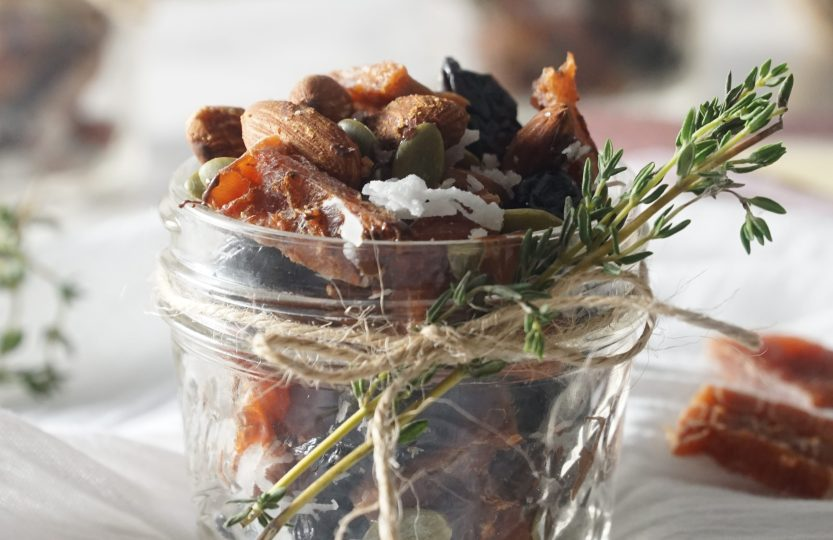 A small jar filled with trail mix decorated with a twine bow and fresh thyme sprigs