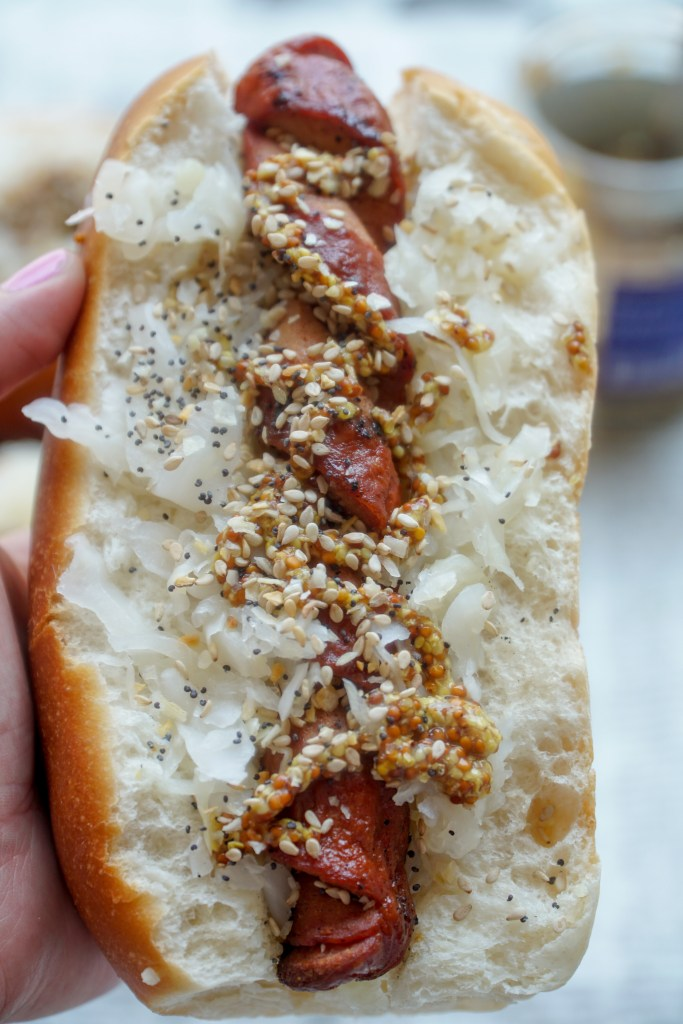 Holding a spiralized hot dog in a bun topped with sauerkraut, spicy mustard, and everything bagel seasoning.