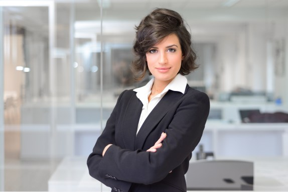 Business woman in an office. Crossed arms