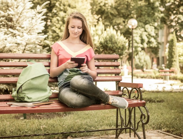 Student in a park on a bench and using tablet PC. Retro styled.