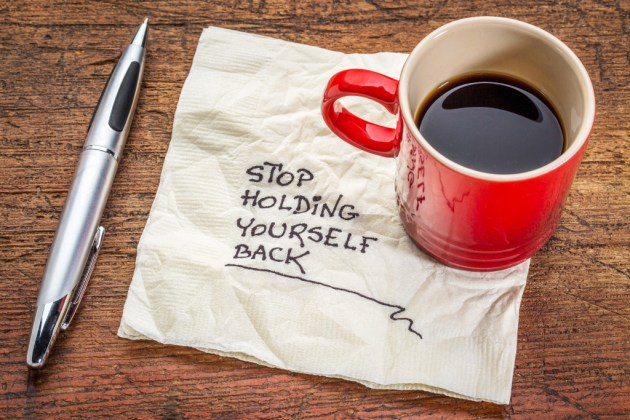 stop holding yourself back - motivational handwriting on a napkin with a cup of coffee