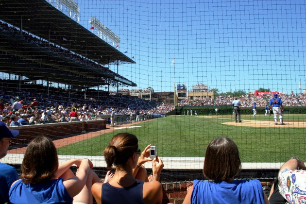 A female fan takes a picture at the baseball game.