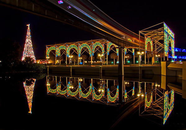 The Walt Disney World monorail streaks through the now-defunct Lights of Winter with Epcot's Christmas tree behind it. This photo was captured in 2008, during the last year of the Lights of Winter.