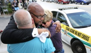 A local pastor prays with those devastated by the Orlando shooting.