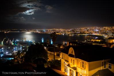 a full moon rises over Valparaiso's busy harbor
