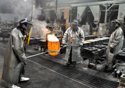 Men dressed for safety position the hot bronze to pour into the sand molds.