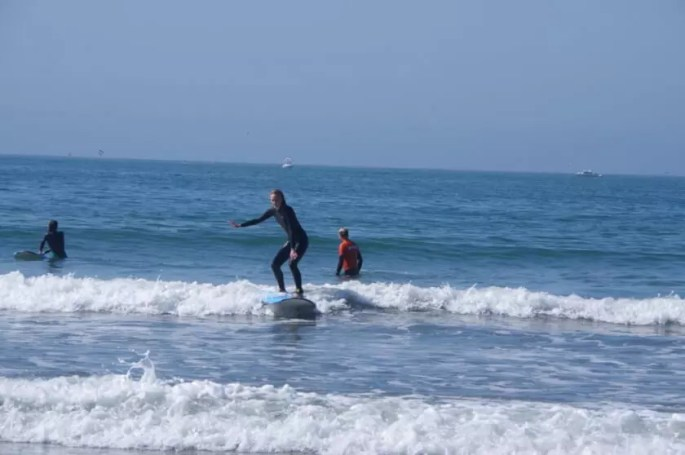 our student catching a wave during her surf lesson