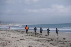 a class is warming up before a surfing session