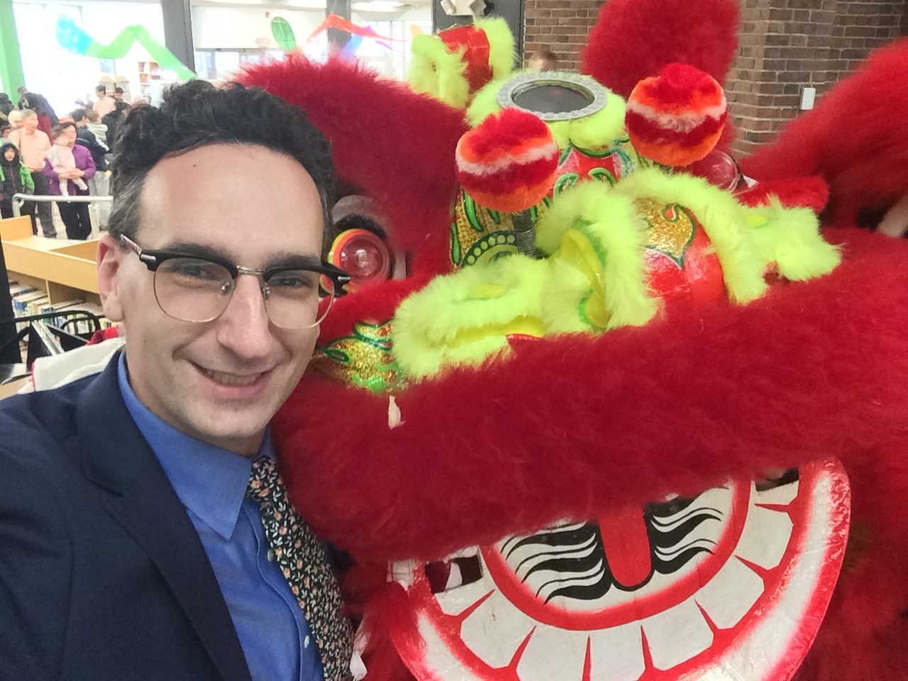 Tommy Vitolo with dragon at Chinese New Year celebration at the Coolidge Corner Library