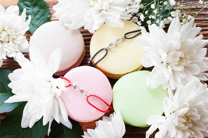 Macaroon french cookies with best friend bracelets. Pretty accessories with infinity sign pendants presented on colorful sweets in blossom frame, close-up