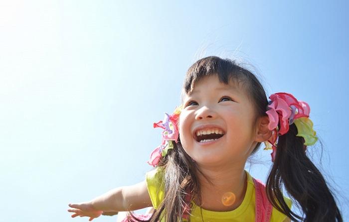 女の子の笑顔と青空のイメージ画像