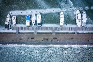 Vertical shot of boats prisoner of the ice in Marken Harbor, Netherlands