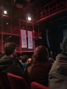 Photograph of protesters intervening at an evening discussion of mobility at the AB in Brussels by unfurling banners.
