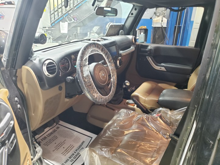 Customer vehicle in for service with a plastic seat and steering wheel cover, as well as a courtesy floor mat.
