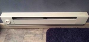 Picture of a typical installation of an electric baseboard heater in bathroom.
