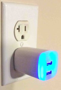 Picture of the GE Jasco Y14 2.1 amp USB Charger Adapter, plugged in, showing the built in LED night light.
