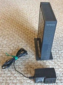 Picture of the Netgear WN802T WAP, unpackaged, shown with its 12-volt power adapter.