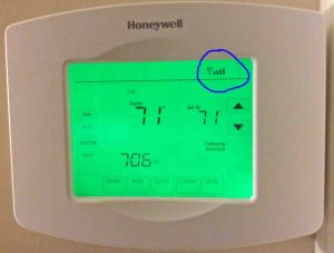 Picture of the Honeywell RTH8580WF Wifi Thermostat, Returned to Normal Operation after successful configuration of a new wireless network, showing the circled wifi status icon in the status area.