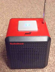 Picture of the Radio Shack 12500 NOAA cube weather radio, operating, with the antenna extended.