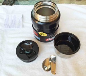 Picture of the Thermos Insulated 16 Ounce Food Jar Completely Disassembled, showing the outer lid, inner cap, spoon and the double walled storage container itself.