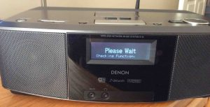 "Picture of the Denon S-32 Internet Radio, Displaying the, ""Please Wait, Checking Function,"" message, just after turn-on."