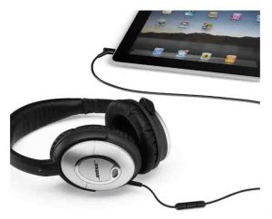 Stock picture of the Bose Quiet Comfort 15 headphones, plugged Into a tablet computer.
