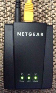 Picture of the Netgear WNCE2001 Universal Internet Adapter, top view, vertical orientation.