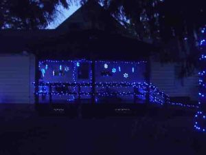 Picture of holiday light decorating outdoors, house south porch. Showing LED snowflakes, and small LED strings on porch railings and banisters.