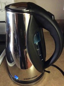 Picture of the Black And Decker® JKC930C Electric Tea Kettle, filled and operating, showing the metric fill gage and water inside, along with the blue-glowing pilot lamp.