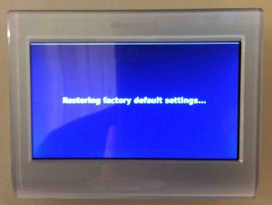 Picture of the Honeywell RTH9580WF smart thermostat, showing the -Restoring Factory Default Settings- screen during reset.
