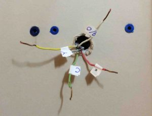 Picture of the wall behind a removed thermostat wall plate, showing the wires protruding.