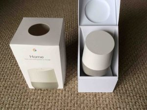 Picture of the Google Home smart speaker, front view, with box open.