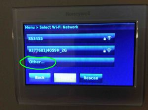Picture of the Honeywell RTH9580WF thermostat, displaying the Select WiFi Network screen, with the Other... option highlighted. How to Fix Honeywell WiFi Thermostat Connection Failure.