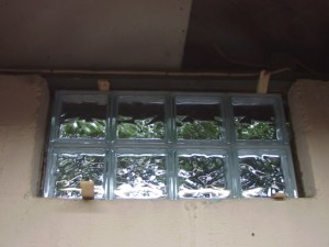 How to install glass block windows. Picture of the first basement glass block window replacement 1, positioned in exterior wall hole and shimmed, prior to mortar application.