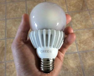 Picture of the Cree™ 100w LED daylight 5000k dimmable A21 light bulb, held in hand.