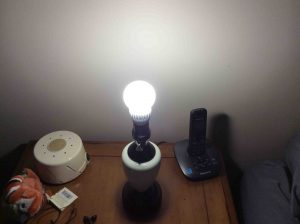 Picture of the Cree™ 60w LED daylight 5000k dimmable A19 light bulb, operating in bedroom lamp, with the shade removed.