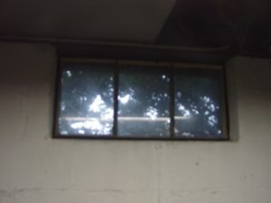 Picture of an old metal framed basement window 1 prior to replacement.
