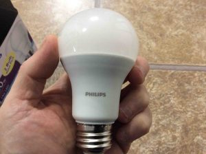 Picture of the Philips LED 100w A19 daylight white light bulb, held in hand.