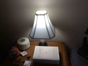 Picture of the Philips LED 100w A19 daylight white light bulb in bedroom lamp, operating.