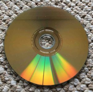 How to fix a DVD that skips and freezes. Picture of the Slightly dusty dual layer DVD disc, showing the gold data side